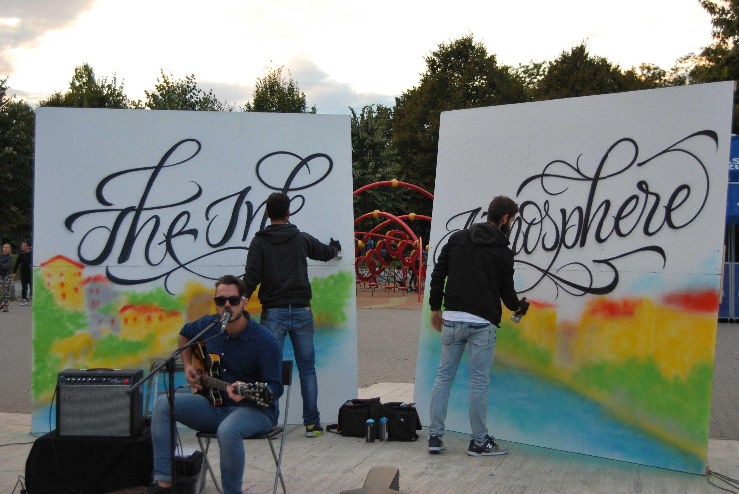 persona suona chitarra e persone dipingono
